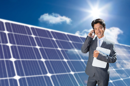 Confident estate agent standing at front door on the phone against solar panel reflecting sunlight