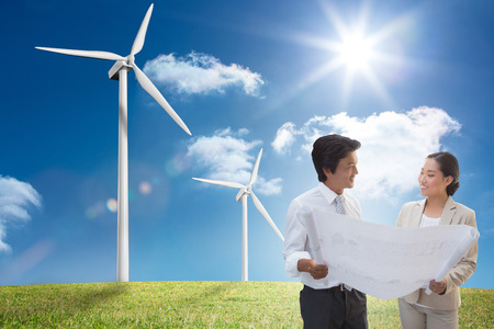 Estate agent looking at blueprint with potential buyer against 54335434 estate agent looking at blueprint with potential buyer against digital landscape with three wind turbines malvernweather Images