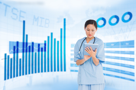 doctor holding money: Surgeon using digital tablet with group around table in hospital against blue data