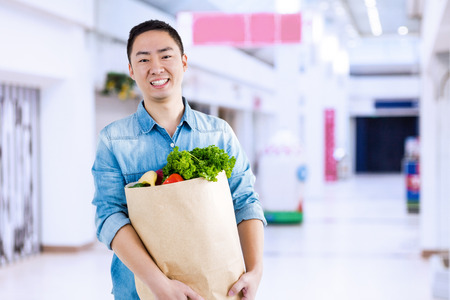 Portrait of man with grocery bag  against interior of modern shopping mall