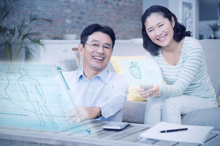 Illustration of human body and head against smiling couple using laptop and smartphone Stock Photo
