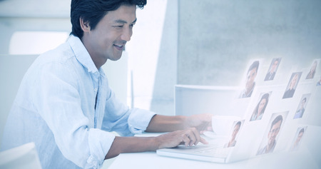 mature business man: Happy man using laptop while having a coffee against portrait of business people
