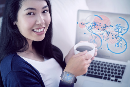 futurist: Asian woman relaxing on couch with coffee using laptop against futurist interface