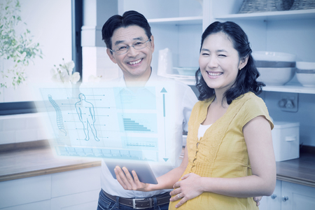 expectant: Illustration of human body  against happy expectant couple using tablet Stock Photo