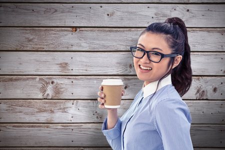 disposable cup: Businesswoman holding disposable cup and looking at wall with notes against digitally generated grey wooden planks
