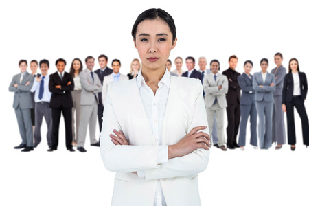 Composite image of serious businesswoman with crossed arms photo
