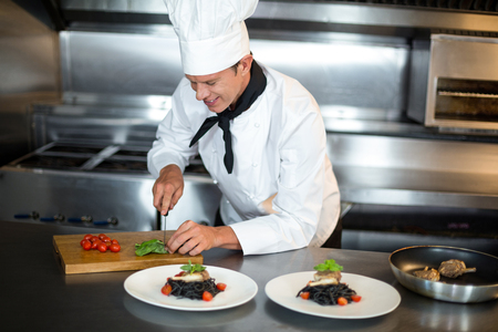 hotel staff: Handsome chef slicing food in commercial kitchen Stock Photo