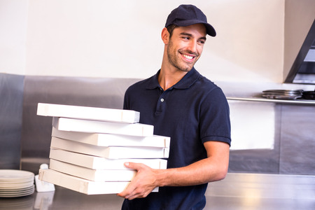 commercial kitchen: Pizza delivery man carrying boxes in commercial kitchen Stock Photo