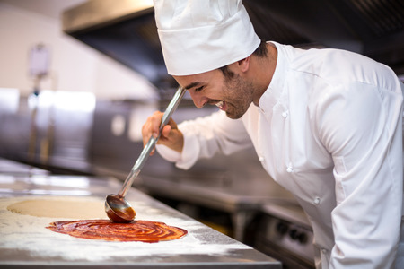 Pizza Chef mettre la sauce à la base dans une cuisine commerciale