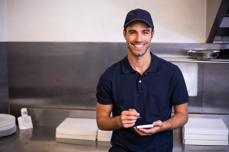 order in: Pizza delivery man taking an order in commercial kitchen Stock Photo