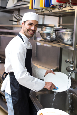 commercial kitchen: Handsome employee doing dishes in commercial kitchen
