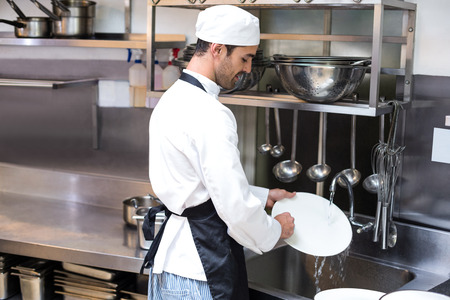 Handsome employee doing dishes in commercial kitchen Stock Photo - 54556153