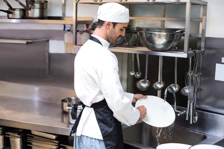 Knappe werknemer afwassen in commerciële keuken Stockfoto