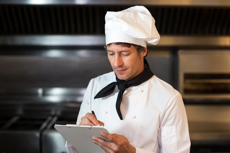 commercial kitchen: Chef writing on clipboard in commercial kitchen
