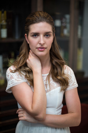 unsmiling: Portrait of serious woman standing at restaurant Stock Photo