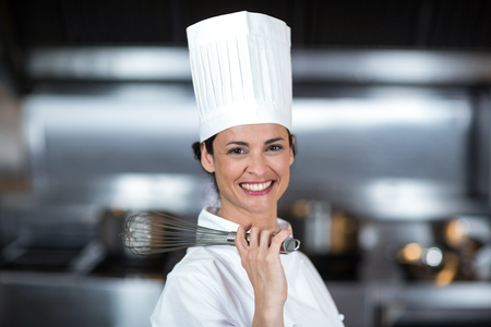 wire whisk: Portrait of smiling female chef holding wire whisk in commercial kitchen