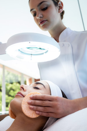 masseuse: Masseuse cleaning woman face with cotton swabs at spa
