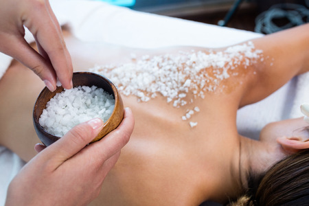 mujeres de espalda: Mujer que disfruta de un masaje exfoliante de sal en el spa