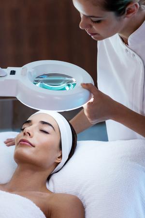 masseuse: Masseuse looking at woman face at spa