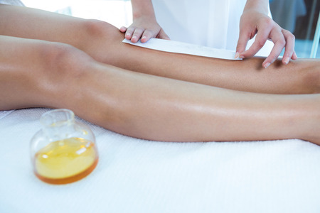 waxed legs: Woman getting her legs waxed at spa Stock Photo