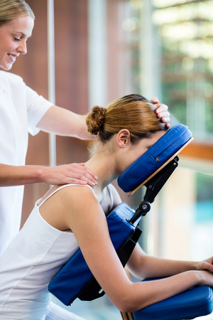 chair massage: Woman receiving massage in massage chair at spa