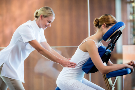 Woman receiving massage in massage chair at spa Stock Photo - 54556619