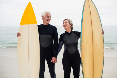 surfboard: Senior couple with surfboard holding hand on the beach on a sunny day Stock Photo