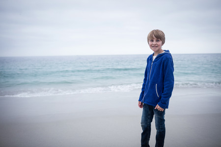 standing alone: Portrait of happy boy standing alone at beach Stock Photo