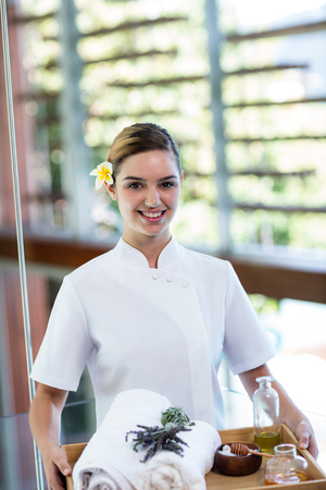 masseuse: Smiling masseuse holding a tray at the spa Stock Photo