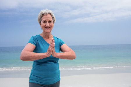 lotus position: Portrait of happy senior woman in lotus position on the beach Stock Photo