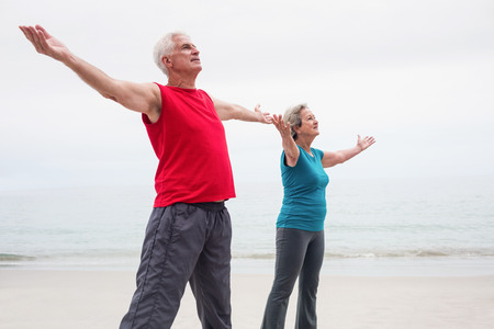 short wave: Senior couple standing with arms outstretched on beach
