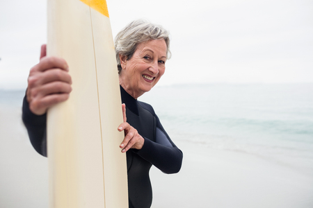 wetsuit: Senior woman in wetsuit holding a surfboard on the beach on a sunny day