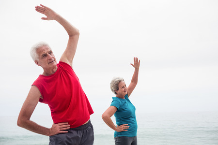 performing: Senior couple performing stretching exercise on beach Stock Photo