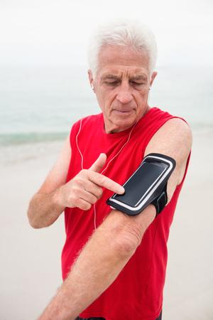 escucha activa: Hombre mayor que escucha la música en su teléfono en manos de la banda para el brazo Foto de archivo