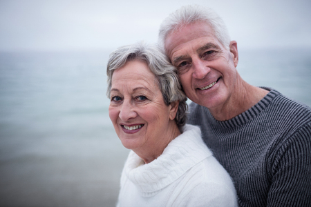 retired couple: Happy senior couple embracing each other on the beach on a sunny day