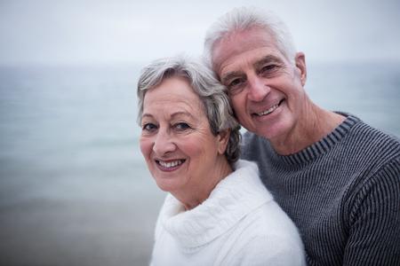 jubilados: Pares mayores felices que se abrazan en la playa en un día soleado Foto de archivo