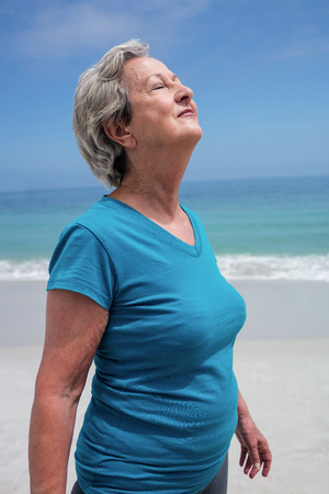 Senior woman with eyes closed standing on the beach on a sunny day