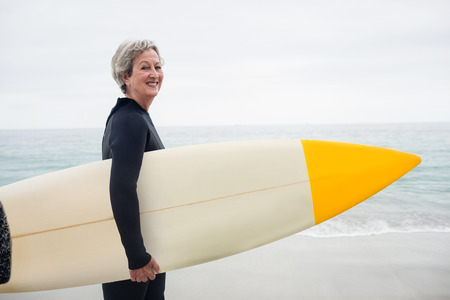 surfboard: Senior woman in wetsuit holding a surfboard on the beach on a sunny day