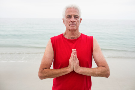 lotus position: Portrait of senior man in lotus position on the beach Stock Photo