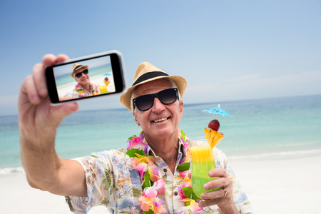 escapism: Happy senior man holding a cocktail glass and taking a selfie on beach