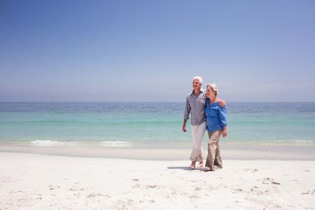 Senior paar wandelen op het strand op een zonnige dag
