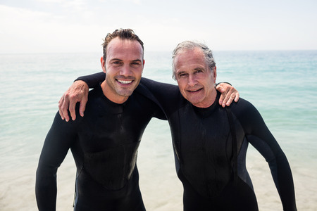 adult offspring: Portrait of happy father and son in wetsuit embracing on the beach on a sunny day Stock Photo