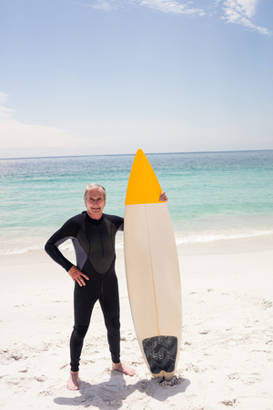 wetsuit: Portrait of senior man in wetsuit holding a surfboard on the beach