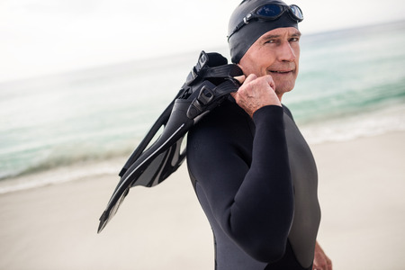 flipper: Portrait of senior man with flipper standing on beach on a sunny day Stock Photo
