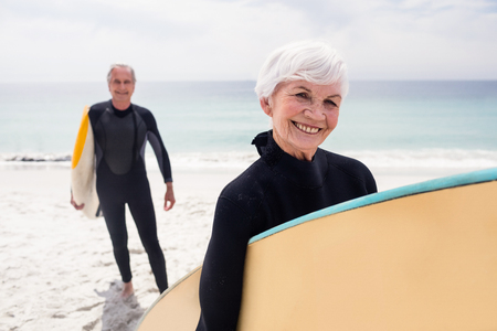 wetsuit: Portrait of senior couple in wetsuit holding surfboard on beach on a sunny day