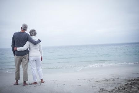 Retrovisione delle coppie senior che abbracciano sulla spiaggia un giorno soleggiato Archivio Fotografico