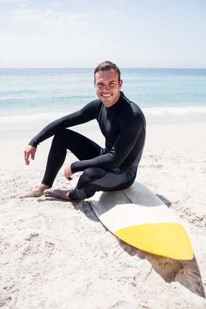 wetsuit: Portrait of surfer in wetsuit sitting with surfboard on the beach on a sunny day Stock Photo