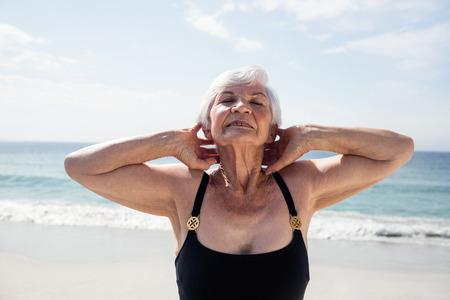 performing: Senior woman performing neck exercise on beach Stock Photo