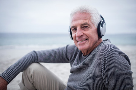 Portrait of senior man listening to music on headphone at beach