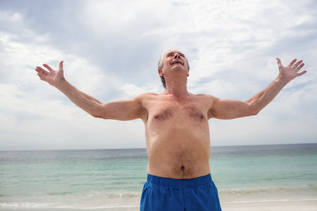 Happy senior man standing on beach with arms outstretched on a sunny day